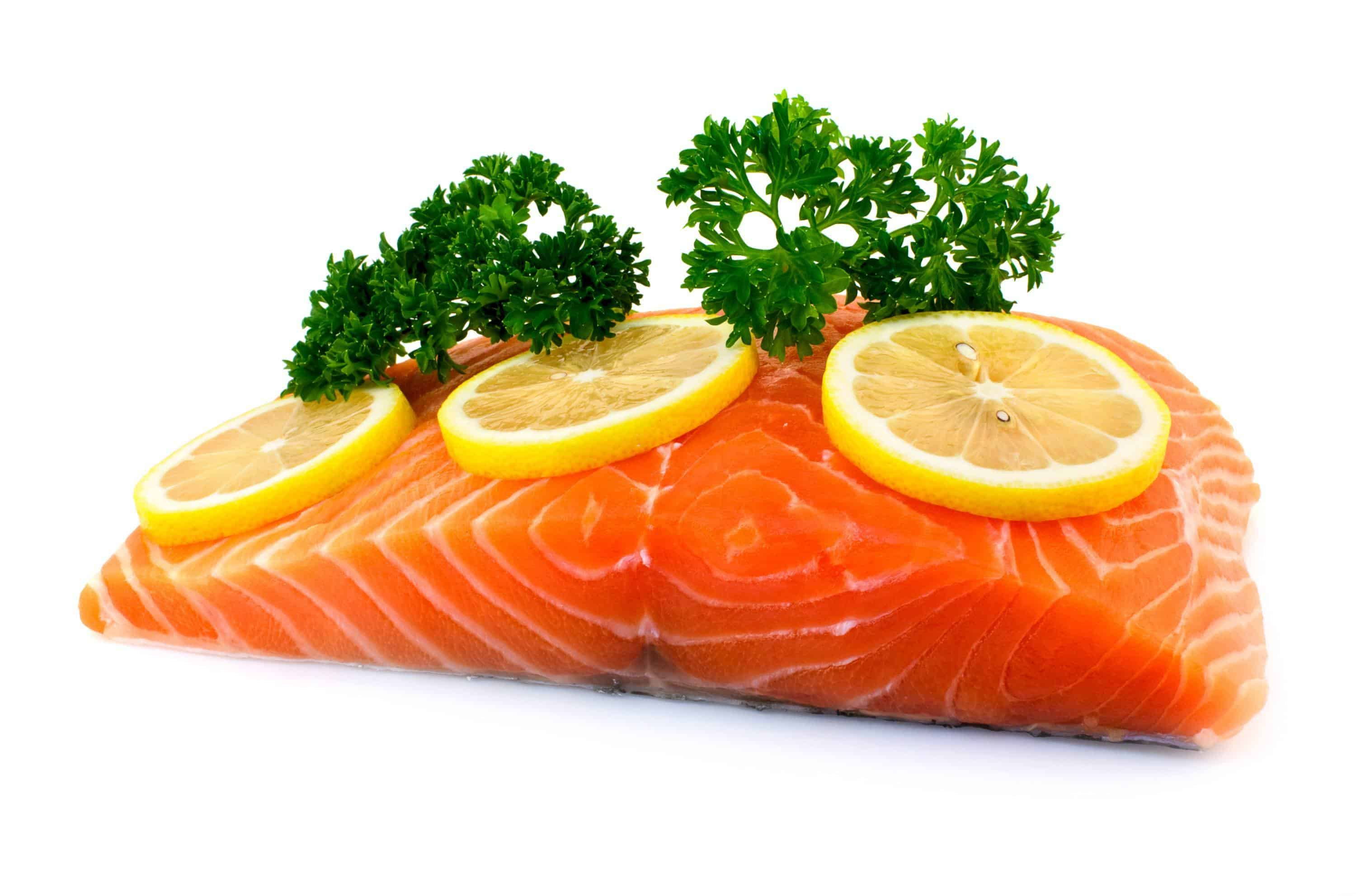 Raw salmon fillet with parsley and lemon on white background