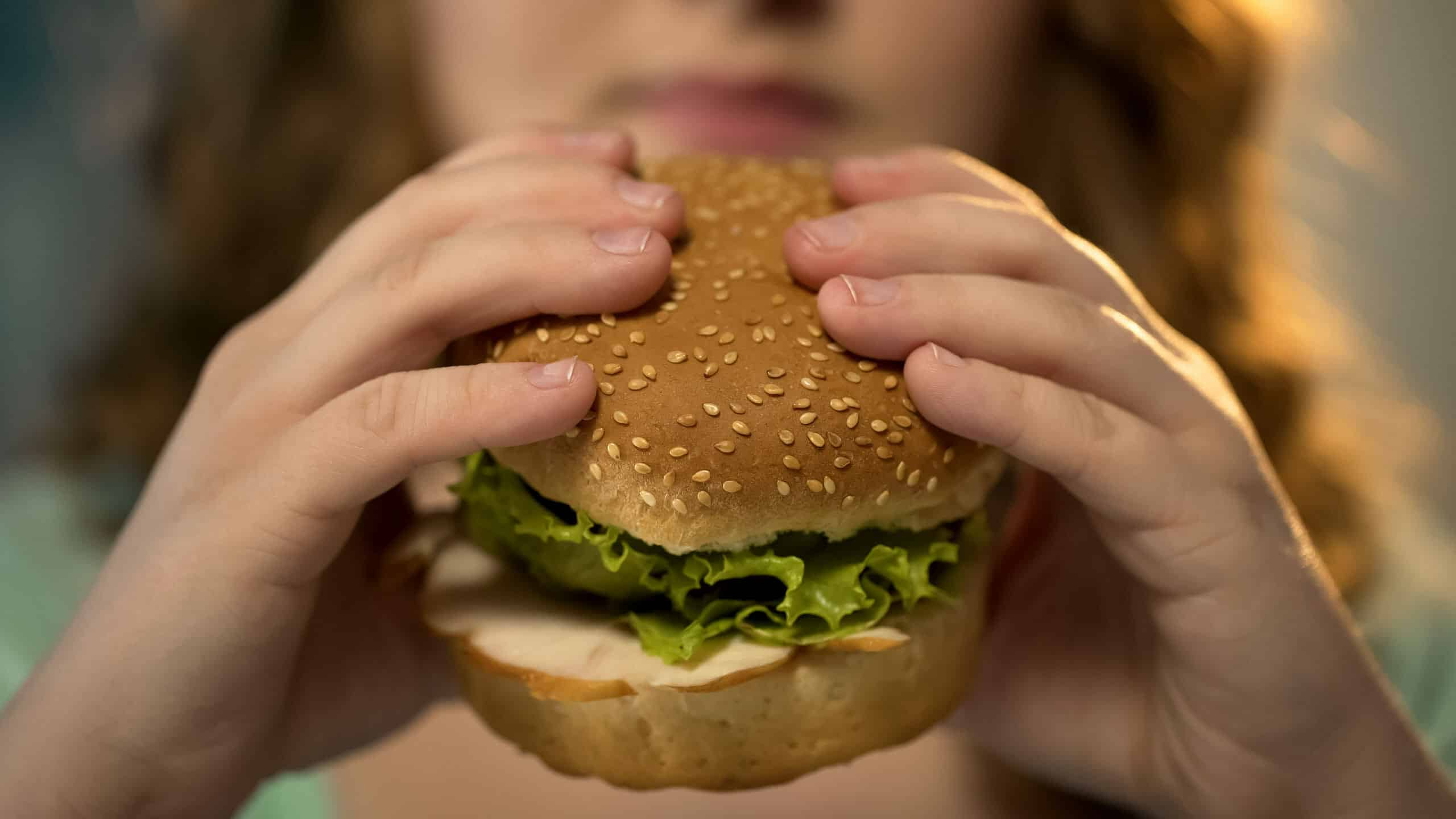 Female biting fast food burger closeup, unhealthy nutrition and overeating