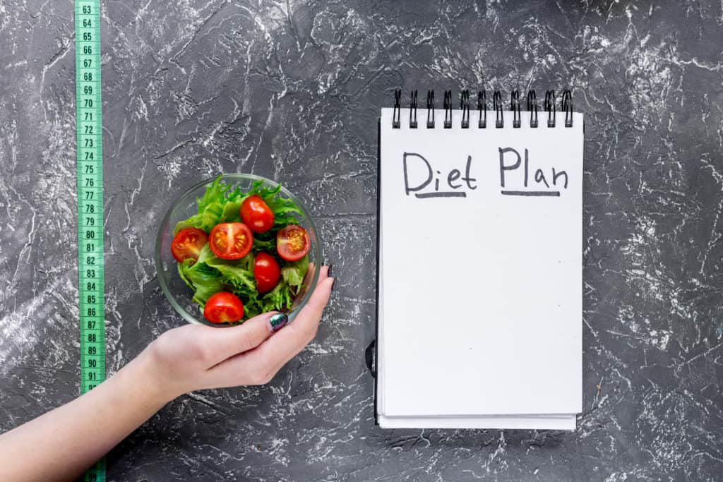 notebook-for-diet-plan-salad-and-measuring-tape-on-grey-stone-table-top-view
