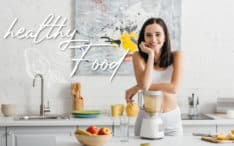 Slim sportswoman smiling at camera while preparing smoothie near measuring tape on kitchen table and healthy food illustration