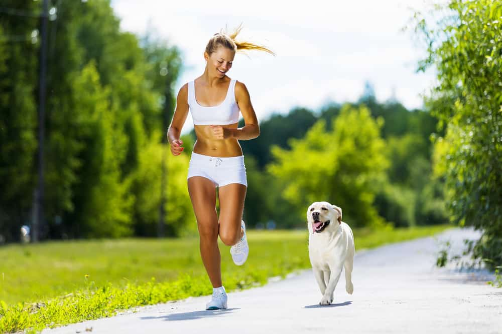 Young attractive sport girl running with dog in park