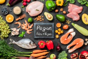Pegan diet conept. Vegan plus paleo diet food ingredients - vegetables, fruits, raw meat and fish on dark background. Top view or flat lay