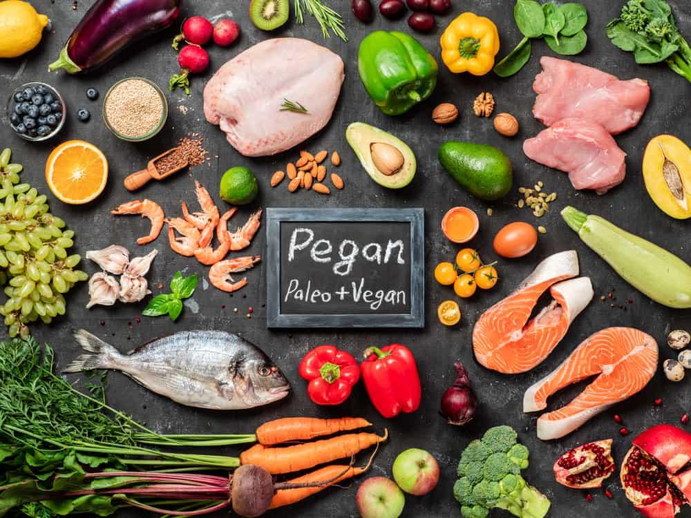 Pegan diet conept. Vegan plus paleo diet food ingredients - vegetables, fruits, raw meat and fish on dark background. Top view or flat lay