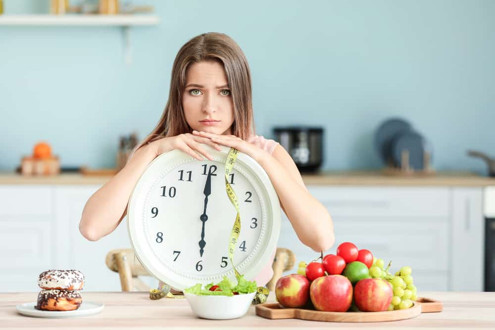 Sad woman with clock and food sitting in kitchen. Diet concept