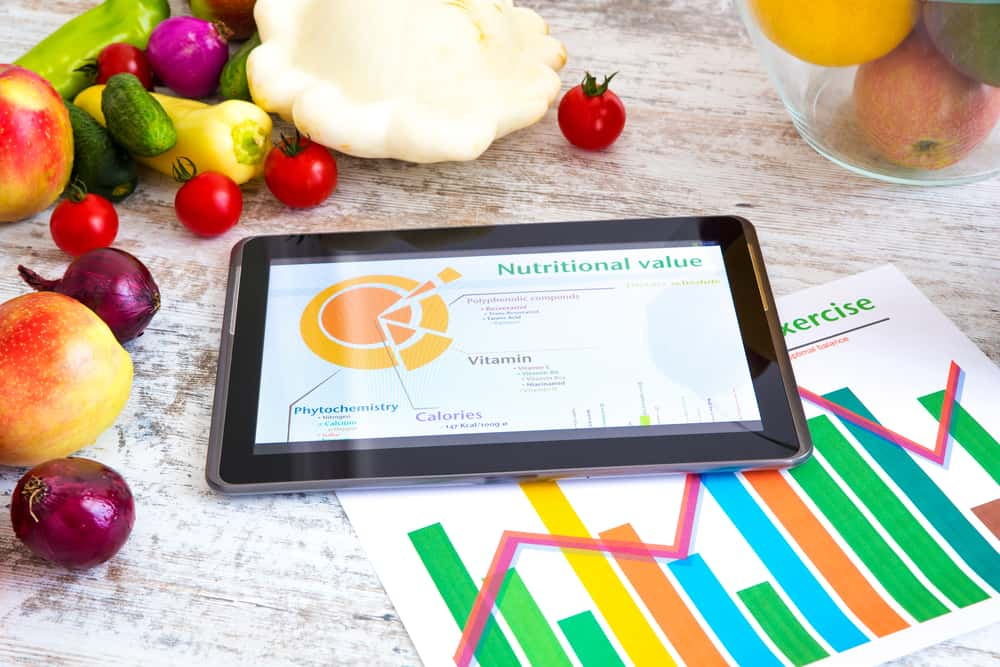 Organic food and a Tablet PC showing information about healthy nutrition and phytochemical composition.