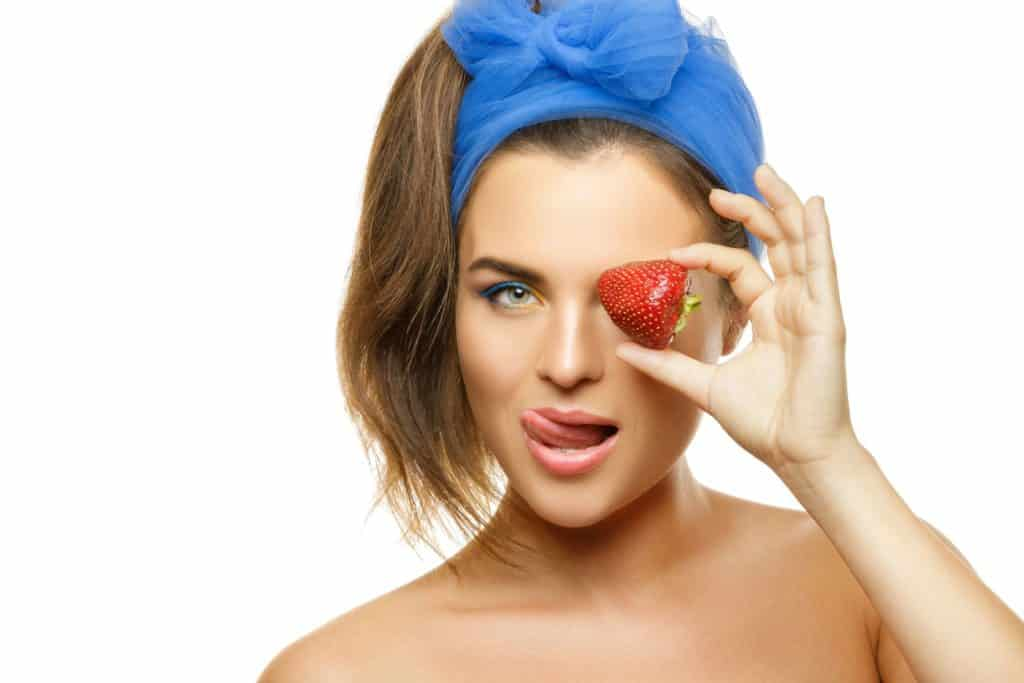 Beautiful woman with colorful makeup and strawberry