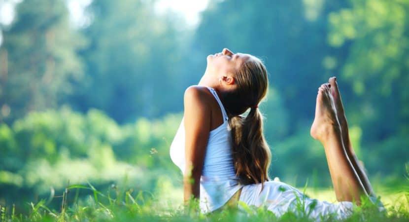 Yoga woman in white on green park grass in cobra asana pose
