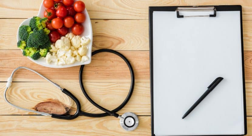 Top view of blank clipboard with pen near stethoscope and tasty vegetables on heart-shape plate