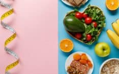Top view of diet food on blue and measuring tape on pink background