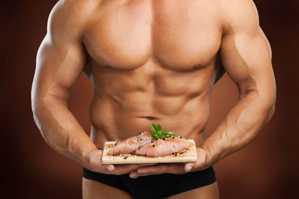 Muscular man holding plate with meat, food for bodybuilder